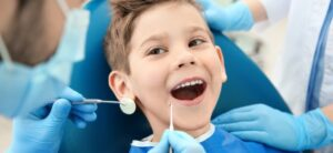 A smiling boy in dentists chair having his teeth examined